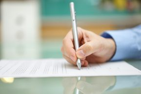 mans hand is  writing document at home on desk