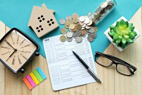 88843347 - business, finance, saving money, property loan or mortgage concept :  top view or flat lay of wood house model, saving account book or financial statement and coins on office desk table